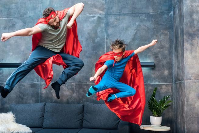 Padre e figlio giocano vestiti da supereroi