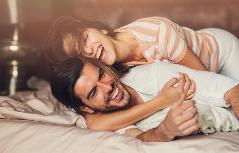 Una coppia sorride abbracciandosi sul letto