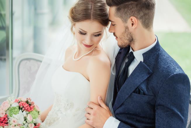 Una giovane coppia di sposi seduta vicino su un divano