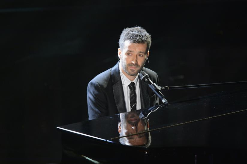 Daniele Silvestri, seduto al pianoforte, in nero, su sfondo nero