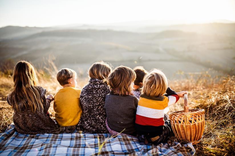 Bambini seduti insieme a fare un picnic