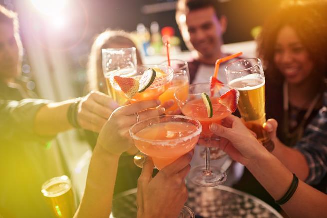 Un gruppo di amici brinda con dei cocktail colorati