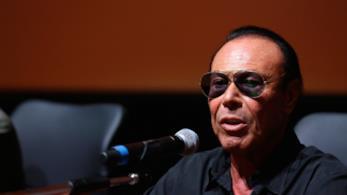 Antonello Venditti in nero, seduto, di fronte al microfono