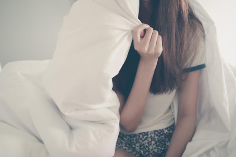 Una ragazza che si copre con il piumone il viso.