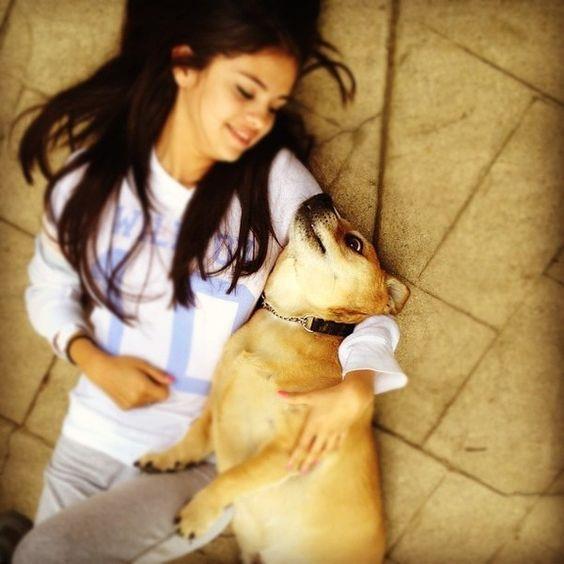 Selena Gomez sdraiata a terra con un cane