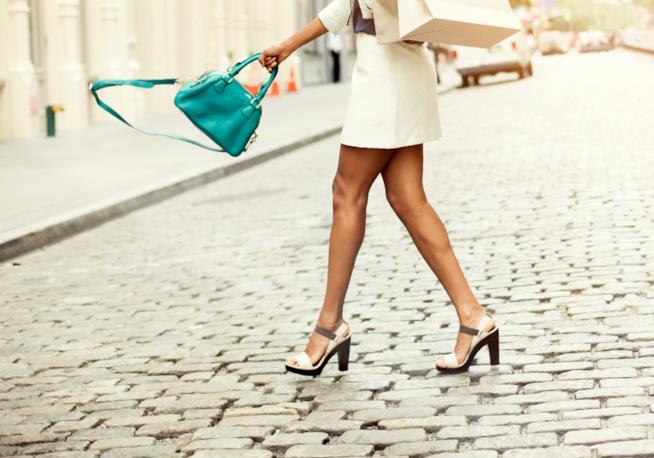 Donna cammina su tacchi alti portando buste
