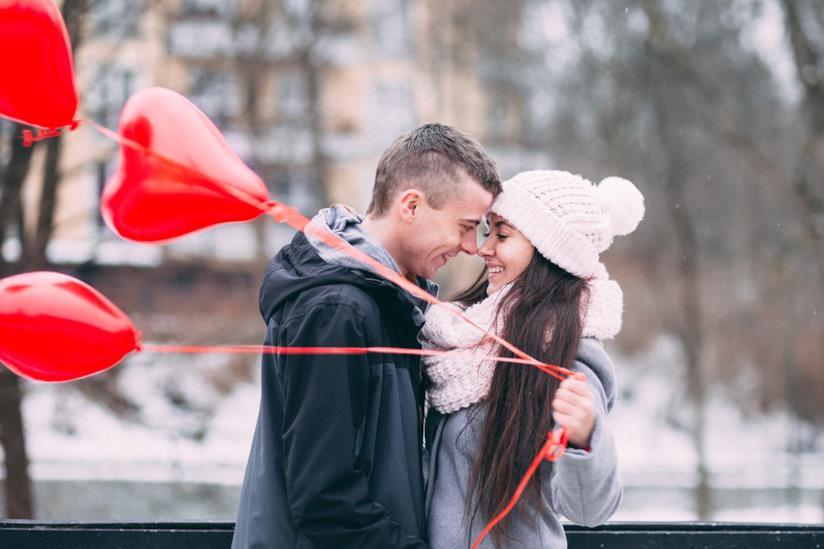 Due fidanzati che si baciano mentre lei tiene dei palloncini