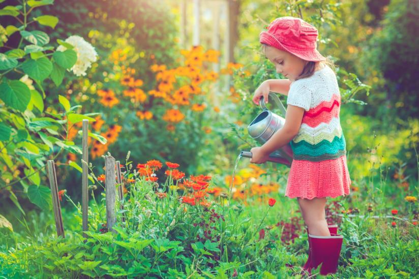 Una bambina innaffia piante in giardino