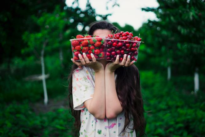 Ragazza tiene in mano un cesto di fragole e uno di pomodori