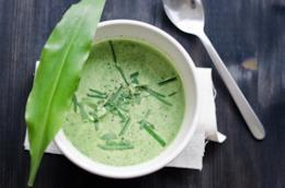 Vellutata verde di aglio orsino in piatto circolare con foglia decorativa