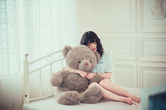 Una ragazza abbraccia un pupazzo sul letto