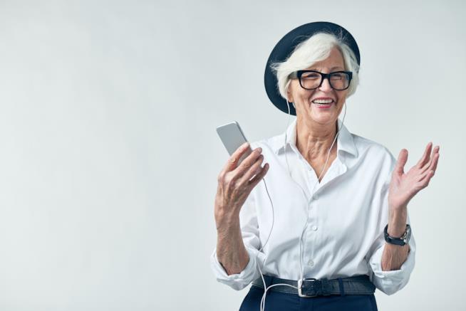 Una signora sorride con il lettore mp3 in una mano