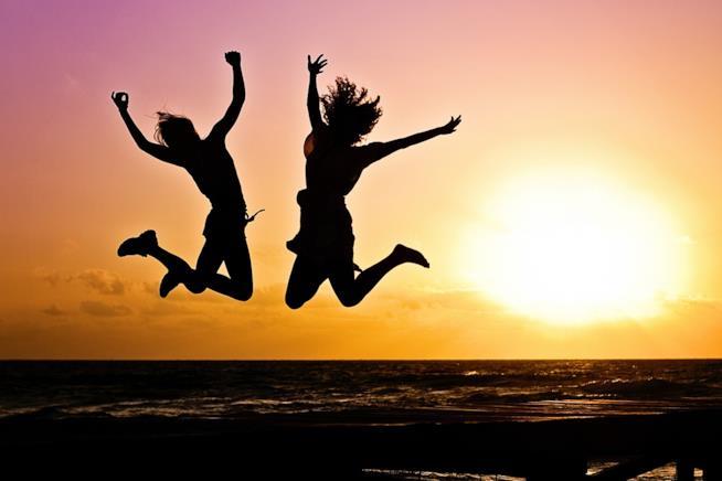 Due ragazze che saltano al tramonto.