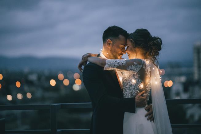 Coppia di sposi abbracciata su un balcone
