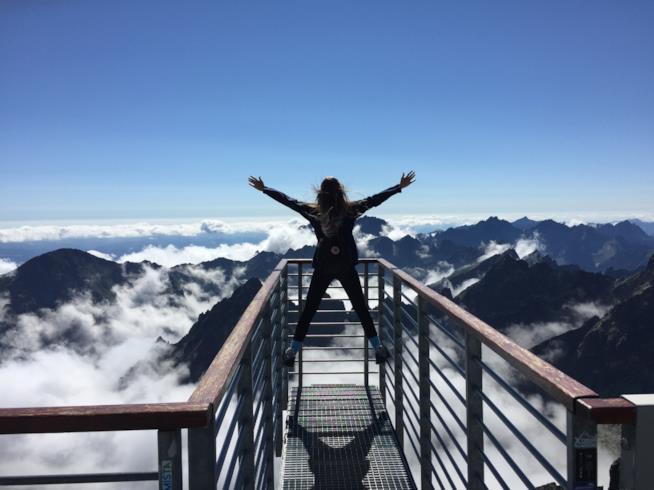 Una donna a braccia aperte su una passerella tra le montagne