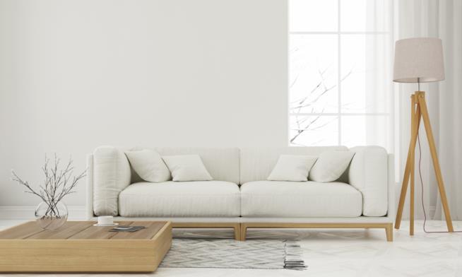 Lampada da terra con base a treppiede in legno e paralume bianco in tessuto posta accanto al divano