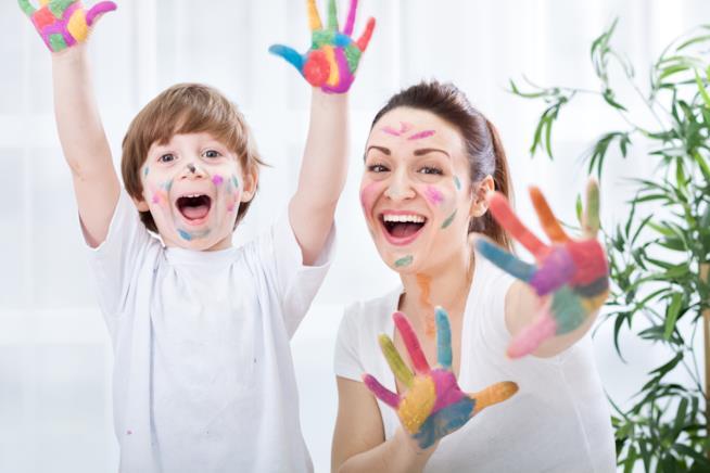 Mamma e bimbo che giocano con la pittura