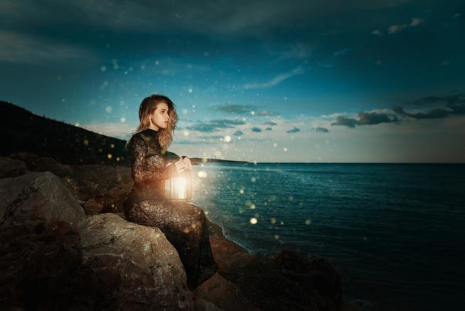 Ragazza seduta su uno scoglio con una lanterna