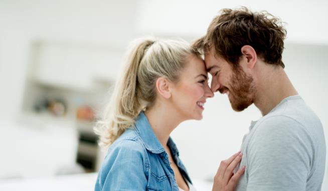 Una donna e un uomo sono fronte a fronte sorridenti