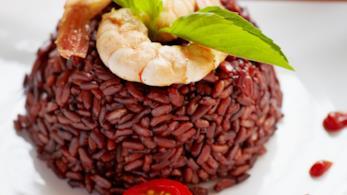 Primo piano di riso venere con gamberi sfumati al Brandy, con foglie di menta e pomodorini