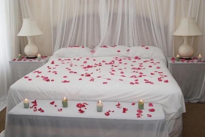 Letto matrimoniale con petali di rosa e candele