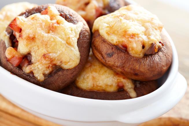 Primo piano di funghi porcini farciti con mozzarella e prosciutto su piatto bianco