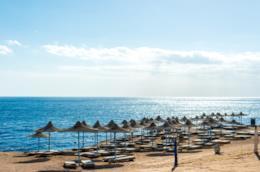 Fila d'ombrelloni lungo una spiaggia dell'Emilia-Romagna