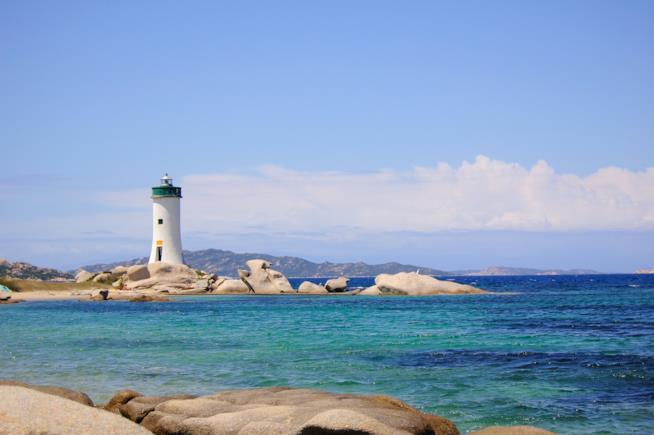 Il mare azzurro, qualche scoglio e un faro sullo sfondo