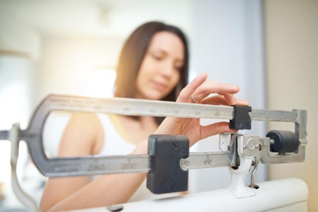 Una ragazza si pesa con la bilancia tradizionale