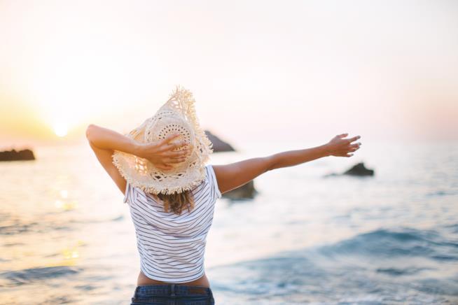 Donna a braccia aperte di fronte al mare