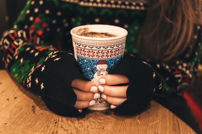 Ragazza tiene tra le mani una tazza di cappuccino