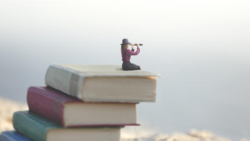 Ragazza seduta su una pila di libri con un binocolo