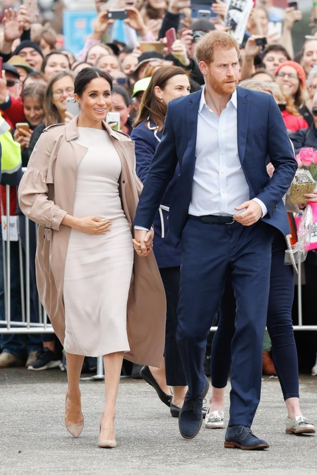 Meghan Markle accarezza il pancione al fianco del principe Harry