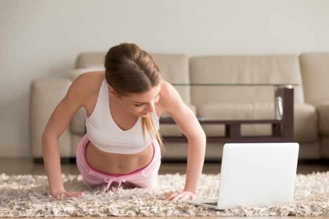 Ragazza si allena a casa seguendo un corso su PC