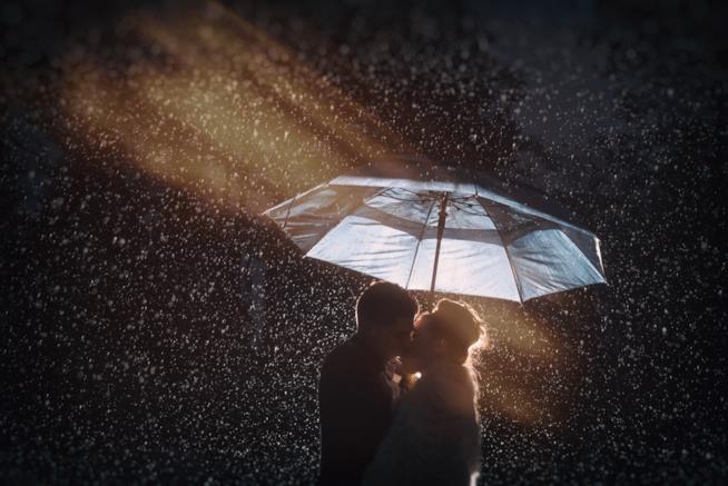 Coppia si bacia sotto la pioggia