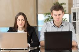 Un uomo e una donna in ufficio si guardano male