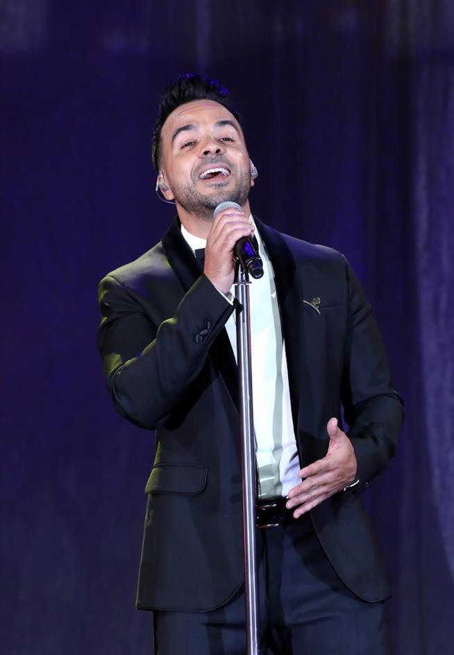 Luis Fonsi, elegante, in piedi, di fronte al microfono