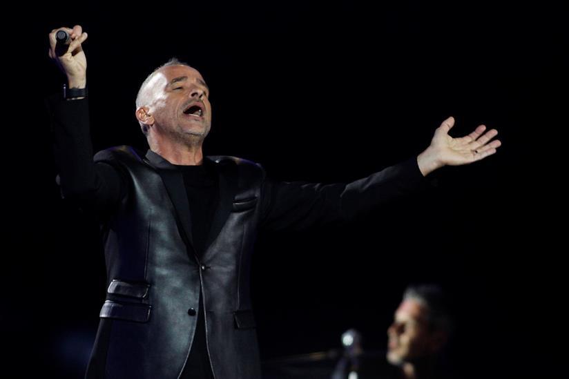 Eros Ramazzotti, innero, su sfondo nero, in piedi, con il microfono in piano e le braccia aperte