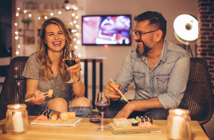 Un uomo e una donna sorridono mentre mangiano sushi seduti sul divano di casa