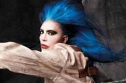 Loredana Bertè, con i capelli blu sciolti, una camicia di forza e con il braccio sinistro sollevato
