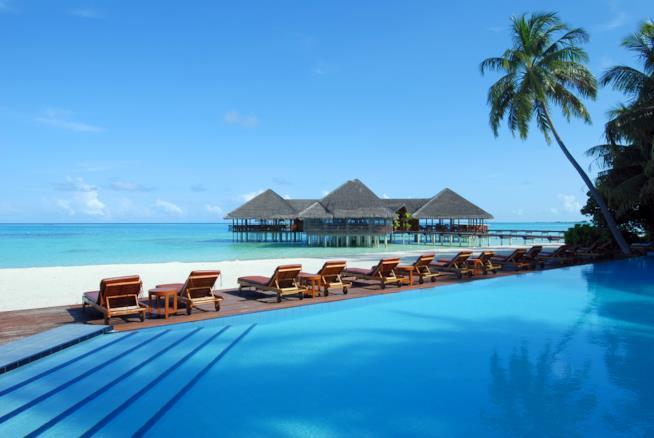 Spiaggia, bungalow e piscina in un resort alle Maldive