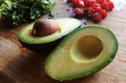 un avocado diviso a metà in primo piano, sullo sfondo dei pomodori a fettine e delle erbe