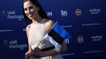 Elina Nechayeva sorride, vestita di bianco, con in mano la bandiera estone