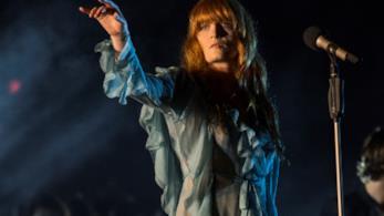 Florence Welch in piedi, davanti al microfono, con un vestito celeste e un braccio alzato