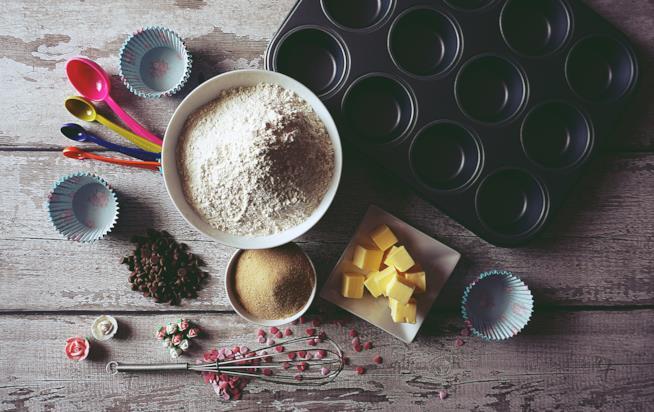 Tavolo con farina, zucchero, burro e stampo per muffin