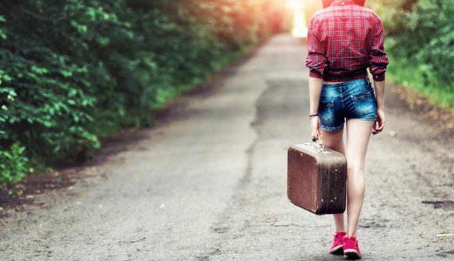 L'immagine di una ragazza di schiena che cammina con una valigia a mano