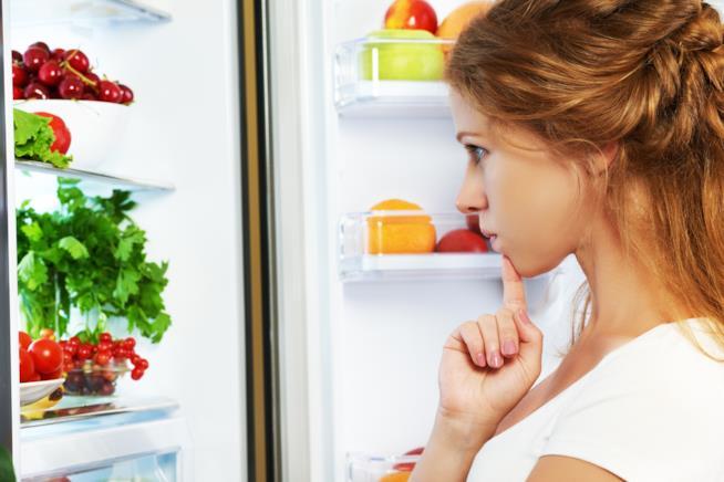 Ragazza guarda perplessa il frigorifero