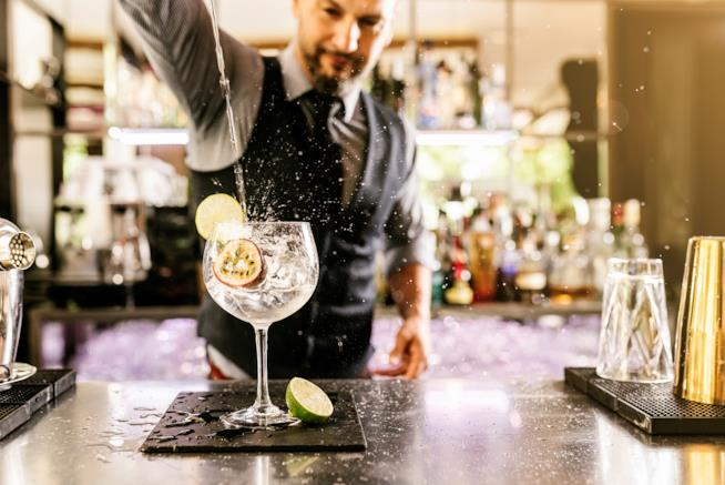Un barman prepara un cocktail all'interno di un bar