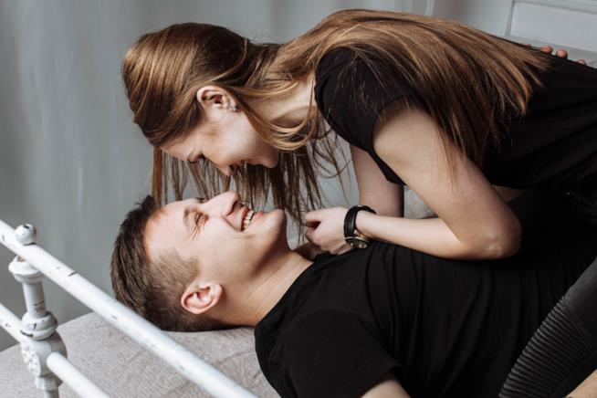 Uomo e donna sdraiati sul letto si guardano sorridendo