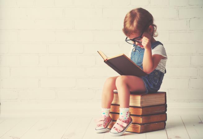 Un bambino seduto sui libri